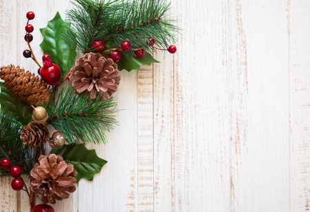 Christmas background with fir branches,pinecones and berries on the old wooden board photo