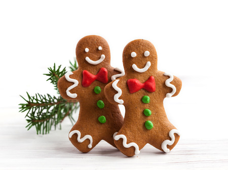 Smiling gingerbread men on white wooden background Imagens