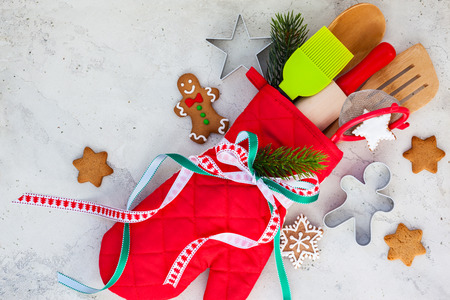 holiday gifts: Christmas gift wrapping idea  with oven mitt,kitchen utensils and cookies Stock Photo