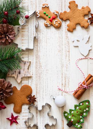 ジンジャーブレッド、クッキー カッター、モミの枝古い木製のボードにスパイスとクリスマスの背景 写真素材