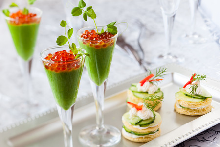 festive appetizers with avocado puree, red caviar and cucumber sandwiches Imagens