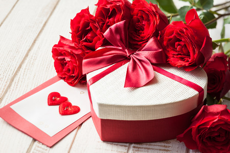Gift box and bouquet of roses for holiday on wooden