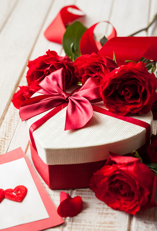 valentines day mother s: Gift box and bouquet of roses for holiday on wooden background