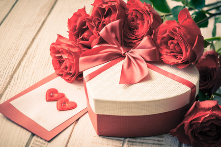 mariage: Coffret cadeau et bouquet de roses pour des vacances sur fond de bois dans le style vintage. Mise au point s�lective, Image teint�e.