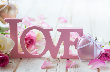 Valentines day concept with letters love and flowers on old vintage wooden background photo