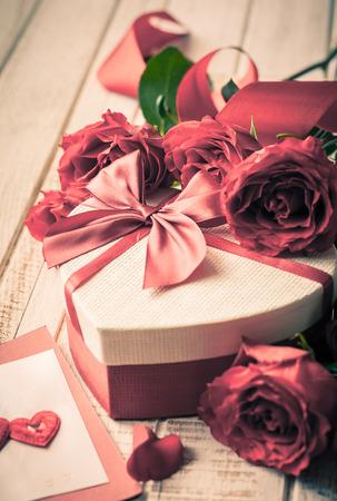 Geschenk-Box und Blumenstrauß der Rosen für Urlaub auf hölzernen Hintergrund im Vintage-Stil. Selektiver Fokus, getönten Bild.