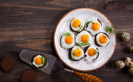canapes: Preparation quail egg canapes with pumpernickel bread for Easter Stock Photo