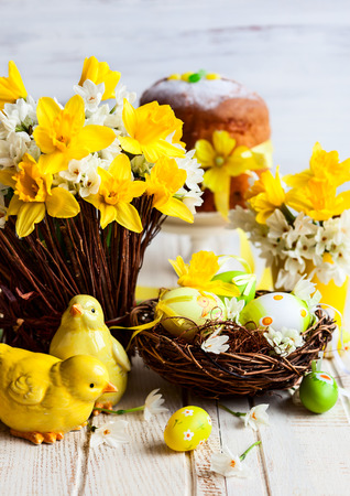 Easter table decoration with fresh daffodils,chick and eggs photo