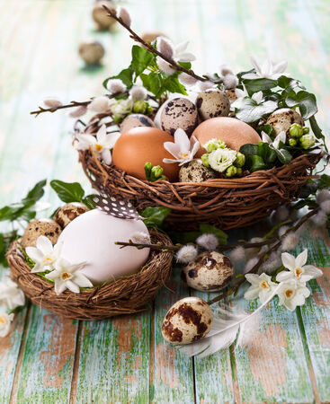 eggs in a nest with flowers,feathers on a wooden table