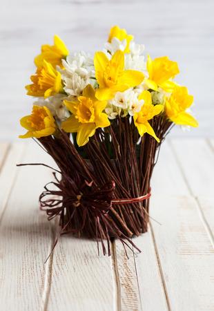 木製のテーブルの上に花瓶に小枝のラッパスイセン 写真素材