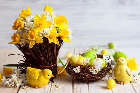 Ostern Tischdekoration mit frischen Narzissen, Küken und Eier