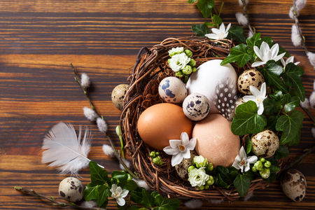 easter nest: eggs in a nest with flowers,feathers on a wooden table