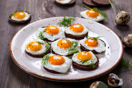 quail egg: Preparation quail egg canapes with pumpernickel bread for Easter Stock Photo