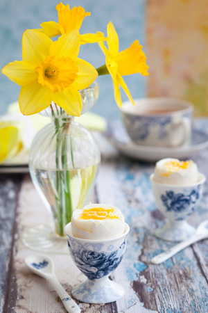 Breakfast table setting with tea, boiled eggs and spring flowers photo