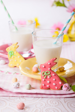 Easter homemade cookies decorated with icing and glasses of milk photo