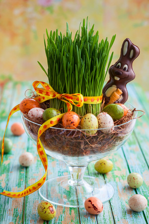 Easter composition with fresh green grass,eggs and chocolate bunny photo