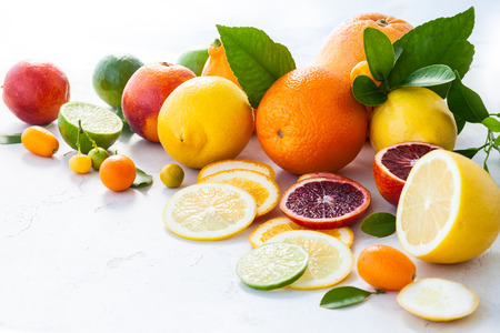 eating fruit: Assorted fresh citrus fruits with leaves
