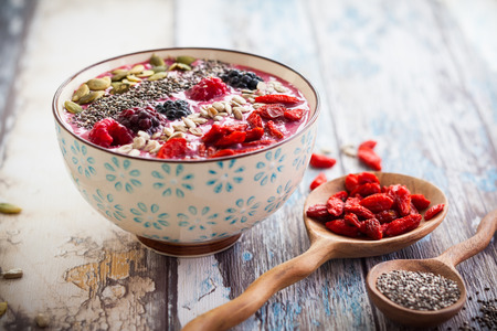 Frühstück Schüssel Beeren-Smoothie garniert mit Goji-Beeren, Himbeere, Brombeere, Kürbis, Sonnenblumen und Chiasamen