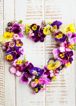 Heart of beautiful fresh flowers on old wooden background Stock Photo - 39293587