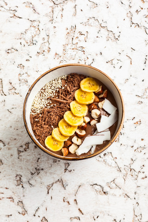 shredded coconut: Chocolate hazelnut smoothie bowl topped with sliced banana, shredded coconut, chopped  chocolate, nuts and sesame seeds.