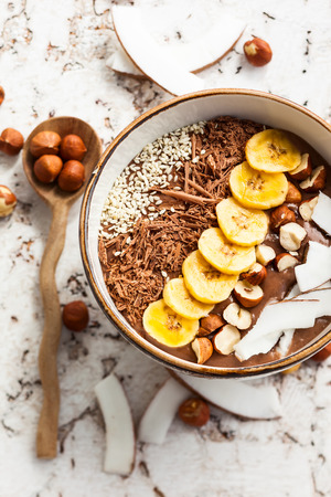 organic raspberry: Chocolate hazelnut smoothie bowl topped with sliced banana, shredded coconut, chopped  chocolate, nuts and sesame seeds.