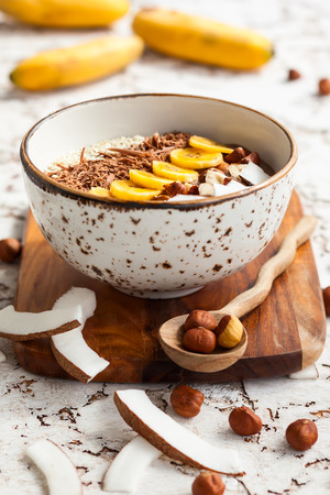 shredded coconut: Chocolate hazelnut smoothie bowl topped with sliced banana, shredded coconut, chopped  chocolate, nuts and sesame seeds. Soft focus