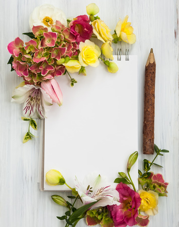 Blank notepad,pen and flowers over white wooden background. Top view with copy space 写真素材