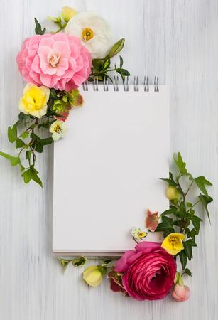 空白のメモ帳と木製の白い背景の上の花です。コピー スペース平面図