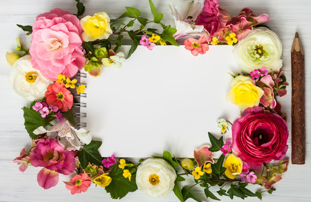 yellow card: Blank notepad,pen and flowers over white wooden background. Top view with copy space Stock Photo