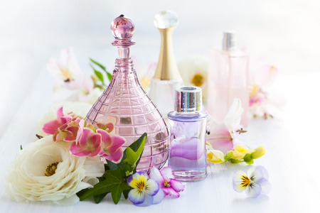 parfum en aromatische oliën flessen omgeven door verse bloemen Stockfoto