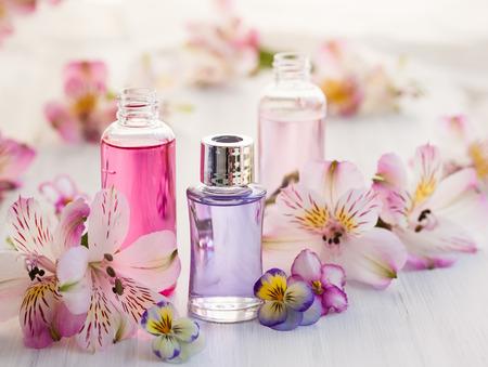 Flessen van essentiële aromatische oliën, omgeven door verse bloemen
