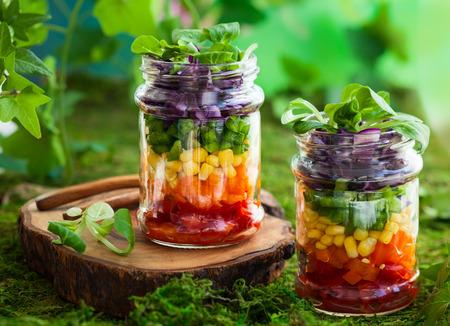 ensalada tomate: Ensalada vegetariana del arco iris en un tarro de cristal para picnic de verano Foto de archivo