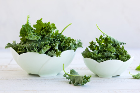 Fresh green kale leaves in  bowl Standard-Bild