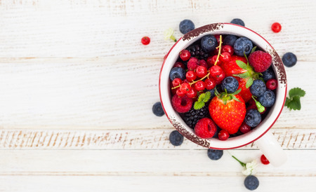 blackberry fruit: Fresh summer berries in vintage mug over wooden backgroundtop view