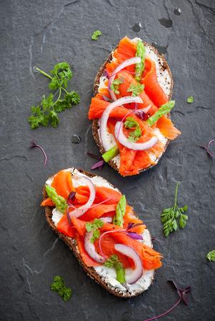 Sandwiches mit geräuchertem Lachs und Spargel auf dem schwarzen Stein Hintergrund Ansicht von oben