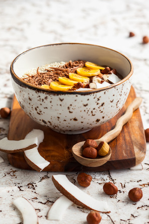 topped: Chocolate hazelnut smoothie bowl topped with sliced banana shredded coconut chopped chocolate nuts and sesame seeds. Soft focus Stock Photo