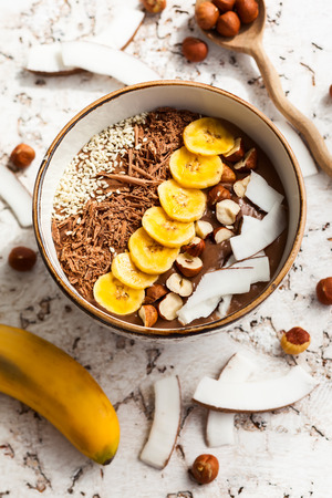 shredded coconut: Chocolate hazelnut smoothie bowl topped with sliced banana shredded coconut chopped chocolate nuts and sesame seeds. Stock Photo