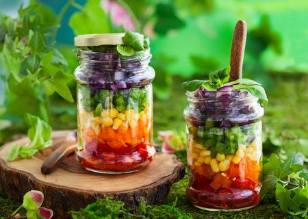 ensalada verde: Ensalada vegetariana del arco iris en un tarro de cristal para picnic de verano Foto de archivo