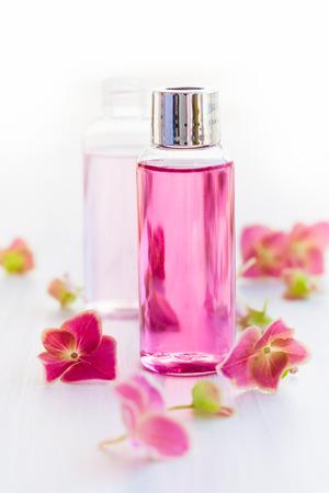 productos de aseo: Botellas de aceites aromáticos esenciales rodeadas de flores frescas