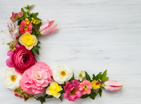 arreglo de flores: Marco de las flores en el fondo de madera blanca. Vista superior con espacio de copia