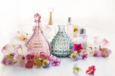 新鮮な花に囲まれた香水および芳香オイル ボトル 写真素材