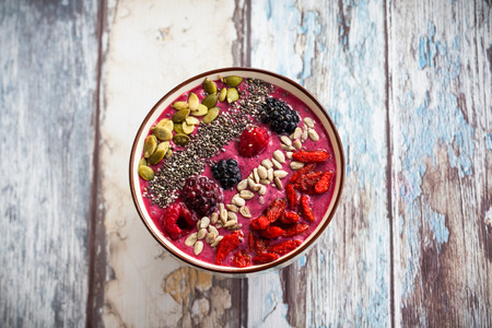 Breakfast berry smoothie bowl topped with goji berriesraspberry blackberry pumpkin sunflower and chia seeds.
