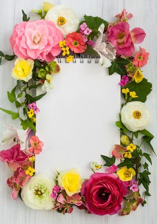 feestelijk: Lege blocnote en bloemen op een witte houten achtergrond. Bovenaanzicht met een kopie ruimte