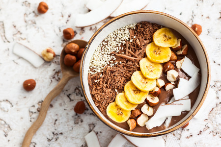 prima colazione: Cioccolato nocciole ciotola frullato condita con fette di banana noce di cocco grattugiata noci tritate cioccolato e semi di sesamo.