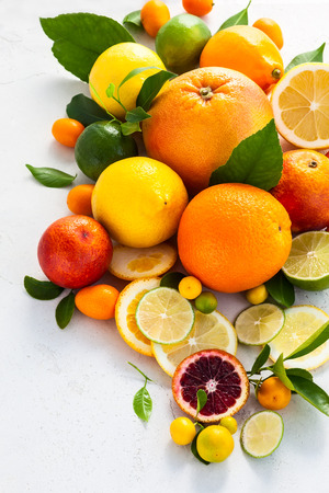 citruses: Assorted fresh citrus fruits with leaves