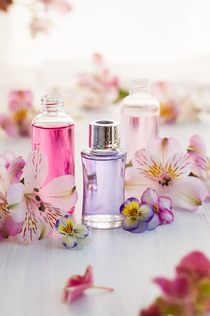 Bottles of essential aromatic oils surrounded by fresh flower
