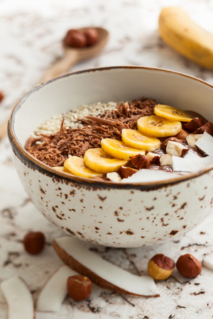 shredded coconut: Chocolate hazelnut smoothie bowl topped with sliced banana shredded coconut chopped chocolate nuts and sesame seeds. Soft focus Stock Photo