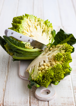head of cauliflower: Half of a romanesco cabbage on a chopping board with a knife