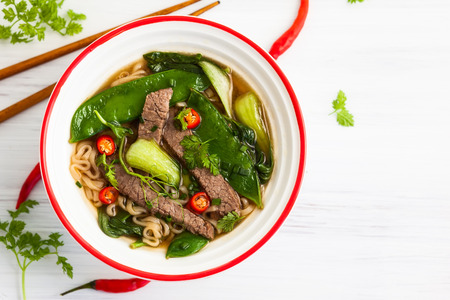Spicy Asian beef soup with noodles and chinese vegetables Standard-Bild