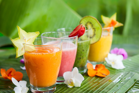 Assortment of fresh  tropical fruits smoothies on the green banana leaves
